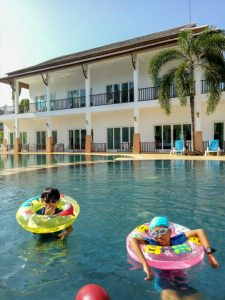 two kids in the swimming pool at nadivana serviced apartment