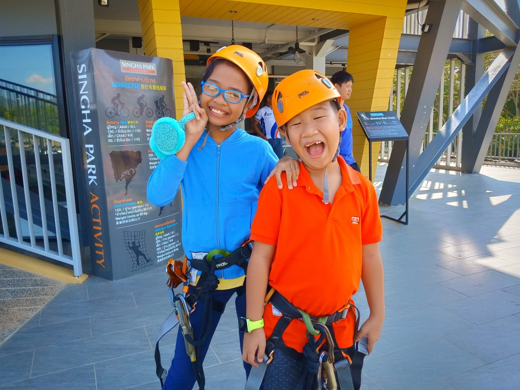 two kids geared up to zipline for the first time